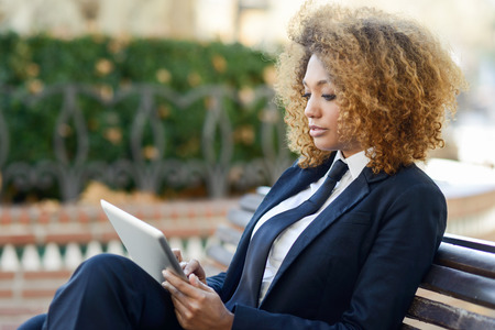 woman hairstyle: Beautiful black curly hair african woman using tablet computer on an urban bench. Businesswoman wearing suit with trousers and tie, afro hairstyle. Stock Photo