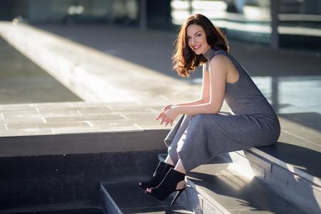 urban fashion: Beautiful young woman, model of fashion, sitting in urban background. Girl smiling.