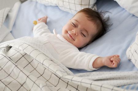블루 시트에 침대에서 자에 누워 웃는 아기 소녀