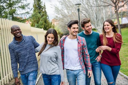 colegios: Grupo de jóvenes multiétnicos que se divierten juntos al aire libre en el fondo urbano