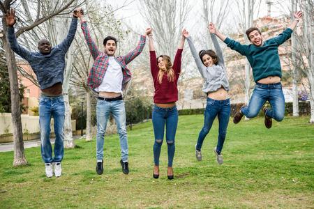 personas saltando: Grupo de jóvenes multiétnicas saltando juntos al aire libre