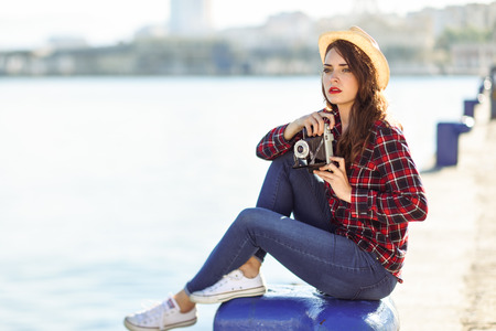 girl in a hat: Young woman taking photographs with a vintage camera sitting in a harbour. Girl wearing plaid shirt, blue jeans and sun hat.