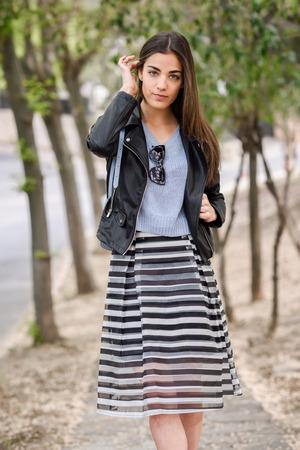 falda: Retrato de una mujer joven que toca su pelo con la mano en el fondo urbano con ropa casual. Chica con falda de rayas, jersey y chaqueta de cuero