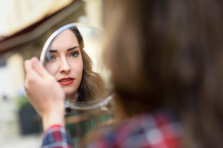 Portrait of young woman looking at herself in a little mirror in urban background. Stock Photo