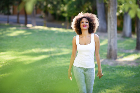 Young black woman with afro hairstyle smiling in urban park. Mixed girl wearing white t-shirt and blue jeans walking on the grass.