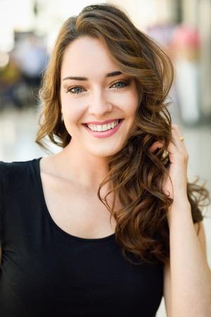 ojos azules: Hermosa mujer joven con los ojos azules que sonríe en fondo urbano. Chica con ropa de verano