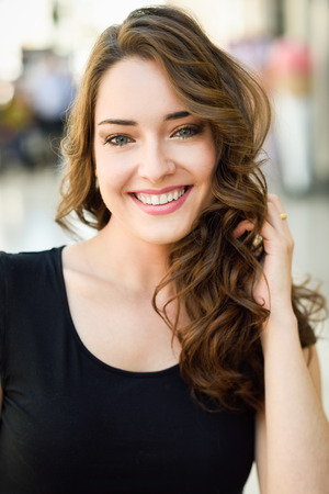 Beautiful young woman with blue eyes smiling in urban background. Girl wearing summer clothes Standard-Bild