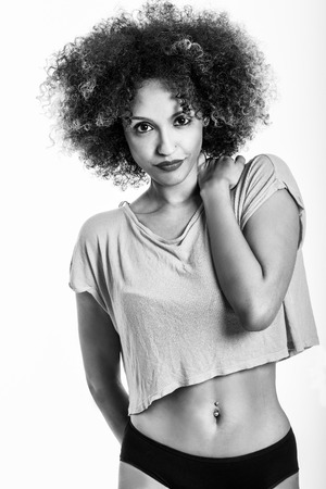 white people: Young black woman with afro hairstyle. Girl wearing t-shirt and black panties. Studio shot.
