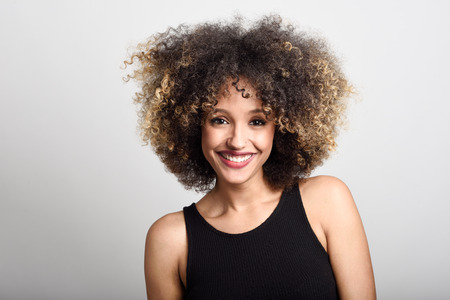 Jeune femme noire avec coiffure afro sourire. Fille portant robe noire. Studio shot.