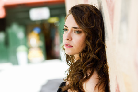ojos azules: Beautiful young woman with blue eyes in urban background. Girl wearing summer clothes