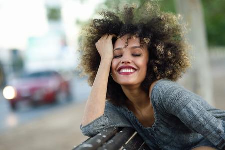 negras africanas: mujer joven negro con peinado afro sonriente en segundo plano urbano. Muchacha mezclada con ropa casual.