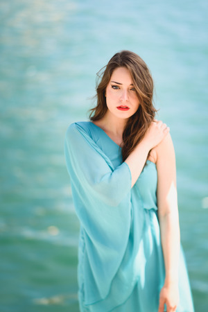 blue sea: Beautiful young woman with blue eyes wearing blue dress in the beach.