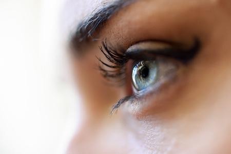 woman eyeball: Close-up of young womans blue eyes with long eyelashes. Make-eye