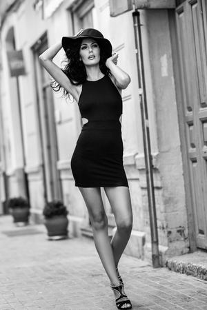 urban fashion: Brunette woman wearing black seductive dress and sun hat in the street. Young girl with curly hairstyle walking in urban background Stock Photo