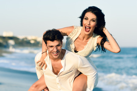 Young happy couple walking in a beautiful beach. Funny Man and woman wearing casual clothes. Male carrying his girlfriend in his arms.