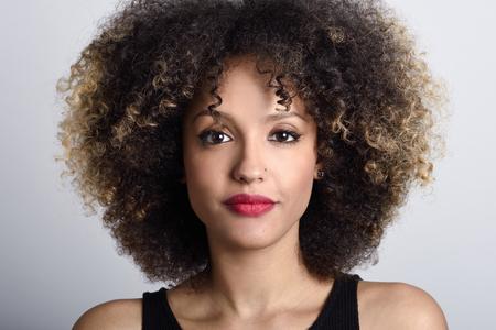 Jeune femme noire avec coiffure afro sur fond blanc. Fille avec coiffure afro. Studio shot.