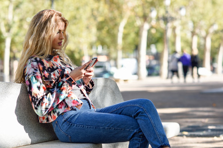 Portrait of blond woman sitting on a bench in the street writting a text message with her smartphone.
