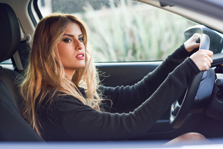 driving a car: Blond young girl driving a sport car looking at the road Stock Photo