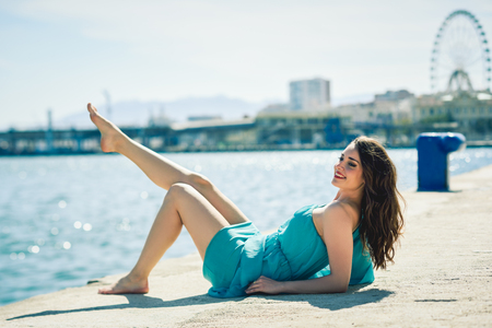 sexy fashion: Beautiful young woman with blue eyes wearing dress in the beach. Happy girl with beautiful legs Stock Photo