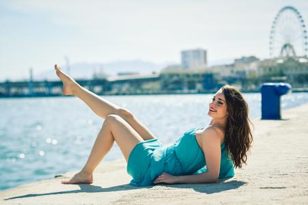 Hermosa mujer joven con los ojos azules que llevan vestido en la playa. niña feliz con las piernas hermosas