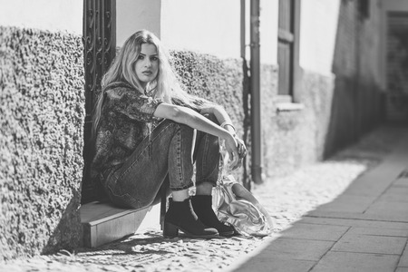 urban fashion: Serious blond woman, model of fashion, sitting on floor in urban background. Beautiful girl wearing shirt and blue jeans.