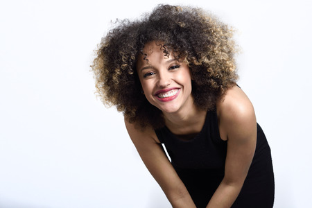 Young black woman with afro hairstyle laughing. Girl wearing black dress. Studio shot.