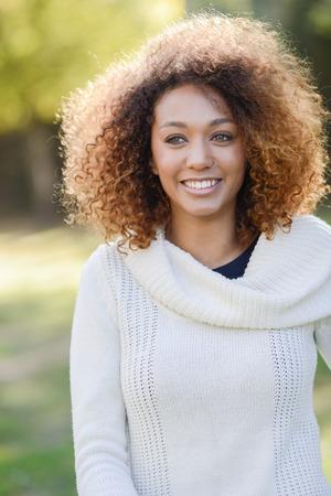ojos negros: mujer africana joven hermosa con el peinado afro americana y ojos verdes con un vestido blanco de invierno con las hojas de otoño en el fondo.