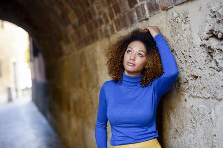 Giovane e bella donna afro-americana, modello di modo, con l'acconciatura afro e gli occhi verdi che indossa un maglione blu sullo sfondo urbano Archivio Fotografico