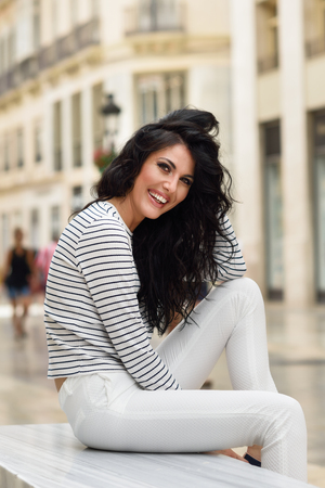 casual fashion: Brunette woman, model of fashion, wearing casual white clothes smiling in the street. Young girl with curly hairstyle sitting in urban background.