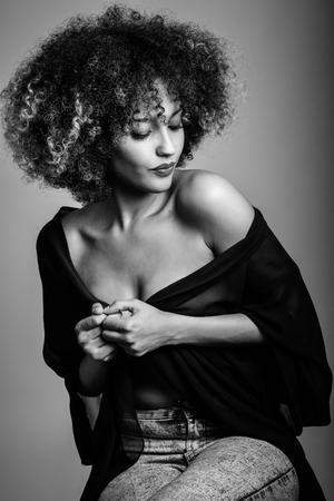 Sexy zwarte vrouw met afro kapsel. Meisje dat zwarte shirt en blauwe spijkerbroek. Studio-opname. Zwart-wit foto. Stockfoto