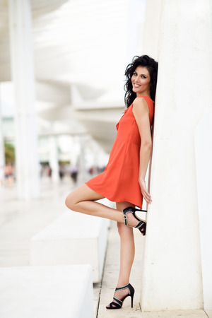 pretty dress: Brunette woman, model of fashion, wearing orange short dress. Young girl smiling with curly hairstyle happy in an urban street. Female with long legs.
