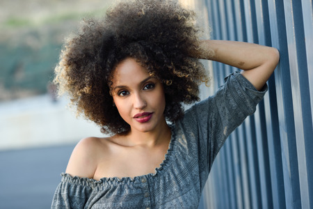 mujeres africanas: la mujer mezclada joven con peinado afro de pie en el fondo urbano. niña de negro con ropa casual.