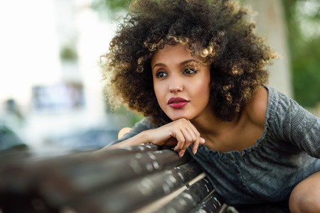 Young black woman with afro hairstyle sitting on a bench in urban background. Mixed girl wearing casual clothes Фото со стока