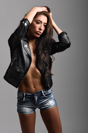 Beautiful woman body in denim jeans shorts and black leather jacket