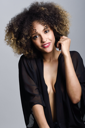 people laughing: Young black woman with afro hairstyle laughing. Girl wearing black clothes. Studio shot.