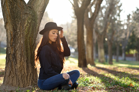 girl in a hat: Portrait of thoughtful woman sitting alone outdoors wearing hat. Nice backlit with sunlight