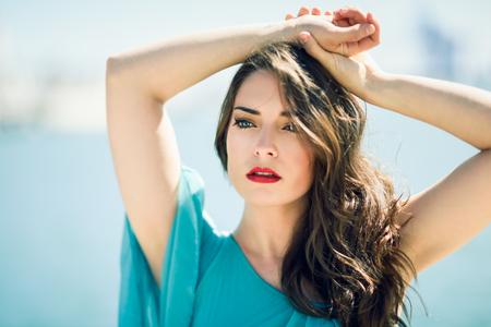 Schöne junge Frau mit blauen Augen im Strand trägt Kleid.
