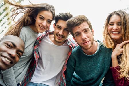 Multiracial group of friends taking selfie in a urban park 写真素材