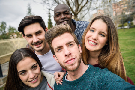urban people: Multiracial group of friends taking selfie in a urban park Stock Photo