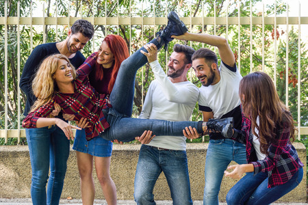 youth group: Group portrait of boys and girls with colorful fashionable clothes holding friend. Urban style people having fun - Concepts about youth and togetherness.