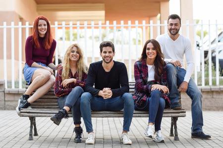 gente sentada: Grupo de jóvenes junto al aire libre en el fondo urbano. Las mujeres y los hombres sentados en un banco en la calle con ropa casual.