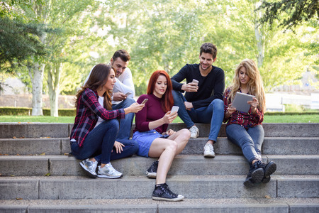 sitting people: Group of young people using smartphone and tablet computers outdoors in urban background. Women and men sitting on stairs in the street wearing casual clothes.