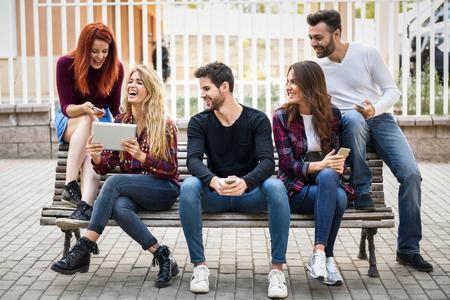 gente sentada: Grupo de jóvenes que utilizan ordenadores teléfonos inteligentes y tabletas al aire libre en el fondo urbano. Las mujeres y los hombres sentados en un banco en la calle con ropa casual. Foto de archivo