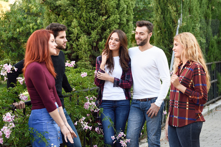 Women and men talking in the street wearing casual clothes. Group of young people together outdoors in urban background.