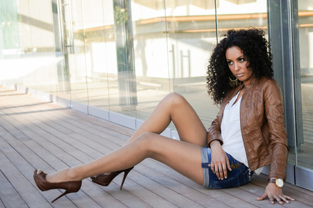 women legs: Portrait of a young black woman, afro hairstyle, wearing beige leather jacket, in urban background Stock Photo