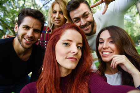 urban people: Group of friends taking selfie in urban background. Five young people wearing casual clothes.