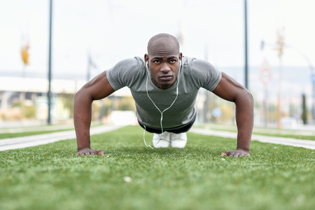 young male: Fitness black man exercising push ups listening to music with headphones. Male model cross-training in urban background. African guy in his twenties doing workout outdoors in the street.