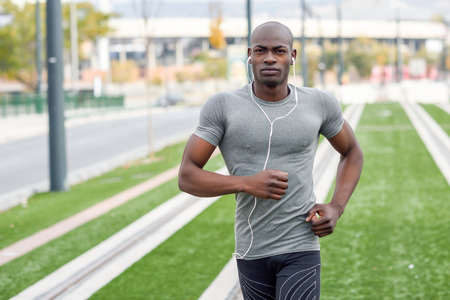 black male: Black man running and listening to music in urban background. Handsome male doing workout outdoors.