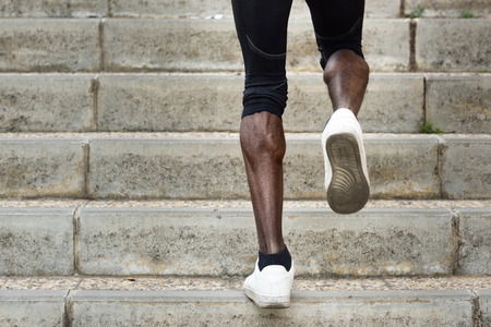 black male: Athletic legs of black sport man with sharp muscles running on staircase steps. African male jogging in urban training workout.