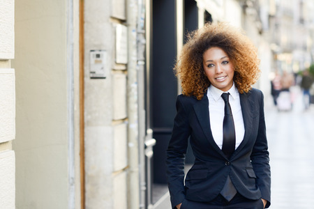 Portrait of beautiful black businesswoman wearing suit and tie smiling in urban background. Woman with afro hairstyle. Stockfoto